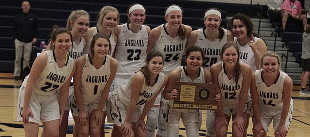 The Mill Valley girls basketball team takes a photo with the Class 5A sub-state championship plaque after its 51-38 victory over Blue Valley Southwest on Saturday.