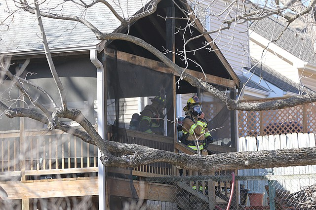 Shawnee firefighters exit the screened in porch of the house at 12600 West 70th Terrace. Investigators say the fire started on the porch.