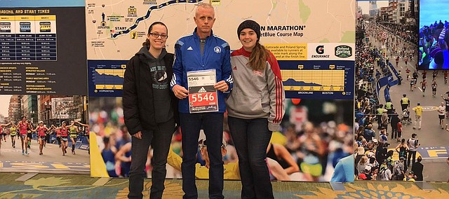 Jack Angell stands with his daughters and his race number at an event celebrating the Boston Marathon.