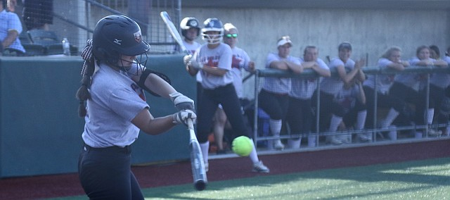 Shawnee Mission North alumna Hannah Redick makes contact with a pitch in Game 1 of the Mo-Kan Softball All-Stars Series on Monday at the Shawnee Mission Softball Complex.