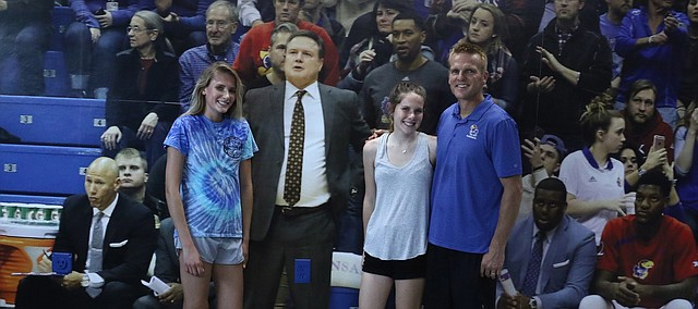 From left, Raegan Ramsdell, Bailey Ramsdell and Rory Ramsdell pose for a photo along the side wall of their garage. The large-plot photo on the wall includes Kansas men's basketball coach Bill Self, his coaching staff and a few of his players. It took two years for Rory to build the garage — which doubles as a mini Allen Fieldhouse.