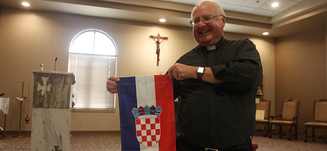 The Rev. Mark Goldasich holds a small version of the Croatian flag Friday at Sacred Heart Catholic Church in Tonganoxie. The longtime Tonganoxie priest, who grew up in the Strawberry Hill district of Kansas City, Kan., is of Croatian descent. Goldasich has caught World Cup fever in rooting for the homeland, as have many in Strawberry Hill.