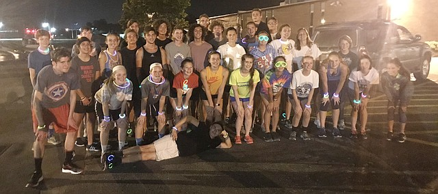 The 2018 Tonganoxie High cross country team gathers before heading out for its first practice of the season in the wee hours Monday. The tradition has continued for several years.