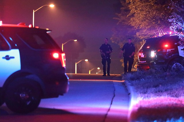 Two Shawnee police officers walk back to their patrol vehicle after assisting Lenexa Police with an overnight standoff near 79th Street and Interstate 435.