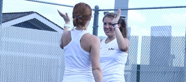 Mill Valley seniors Anika Roy (right) and Josie Carey (left) high-five each other after winning a point in their doubles match of Tuesday's home dual against Bonner Springs.