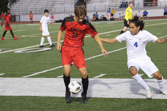 Shawnee Mission North soccer sophomore Dayton Moody (No. 13) fights for a ball against Gardner-Edgerton High School Tuesday night at Shawnee Mission North High School.