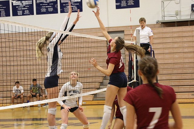 St. James Academy volleyball junior Lauren Kropf (No. 12) hits the ball against Blue Valley North High School Tuesday night at Blue Valley North High School.