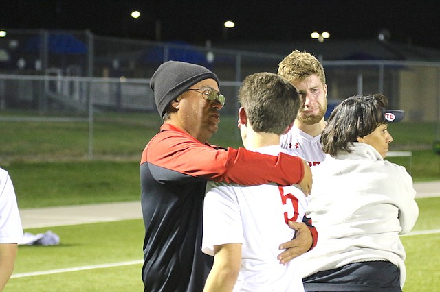 Shawnee Mission North High School soccer head coach Jaime Velez (left) hugs senior Jack Spencer (No. 5, right) following a playoff loss to Olathe Northwest High School Tuesday night at the College Boulevard Activity Center in Olathe.