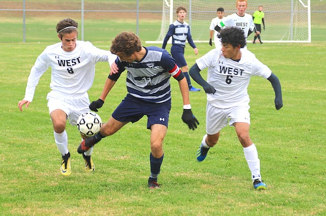 Mill Valley High School soccer senior Jake Ashford (No. 11) tries to control the ball against Shawnee Mission West High School in a Regional finals match Thursday at Mill Valley High School in Shawnee.