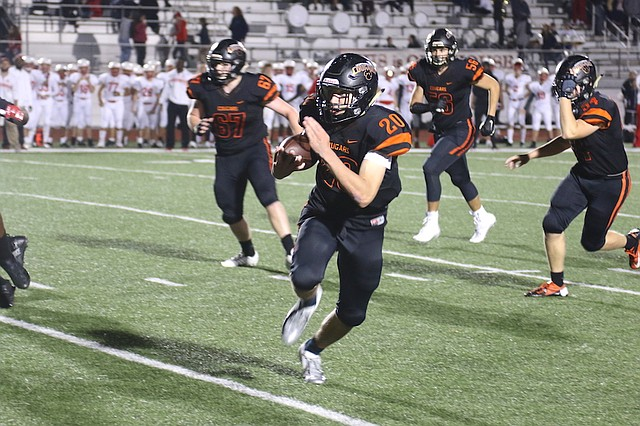 Shawnee Mission Northwest football sophomore quarterback Ty Black (No. 20) runs the ball against Shawnee Mission North High School Friday night at Shawnee Mission North High School.