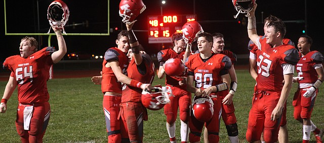 Tonganoxie High quarterback Hayden Robbins embraces fellow senior Korbin Riedel as the rest of the THS football team also celebrates Friday's 48-36 playoff victory against Chanute.