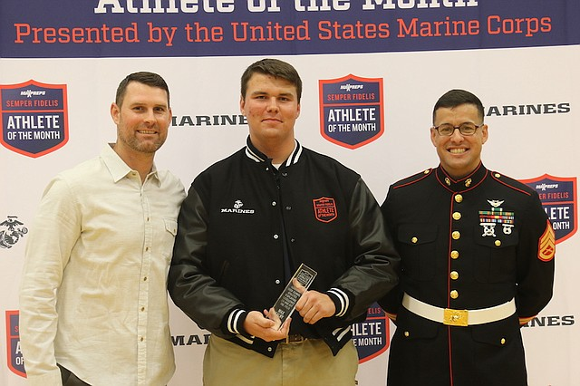 St. James Academy football junior Max Kalny (center) poses with Kansas City Chiefs quarterback Chad Henne (left) and a member of the United States Marine Corps (right) after accepting the MaxPreps Semper Fidelis High School Athlete of the Month award Tuesday afternoon at St. James Academy.