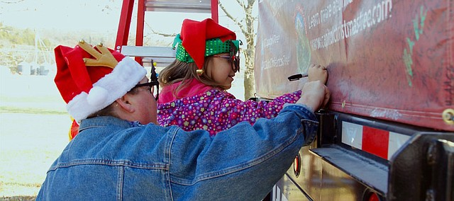 Barb McGoyne, of Topeka, lifts her niece, Sophia Hoppas, 7, so that she can sign a tarp concealing the Christmas tree that will be displayed on the U.S. Capitol grounds. They were among the about 1,000 people who viewed the tree and semitruck transporting it from Oregon to Washington, D.C., during a Tuesday, Nov. 20, 2018, stop at Perry-Lecompton High School.