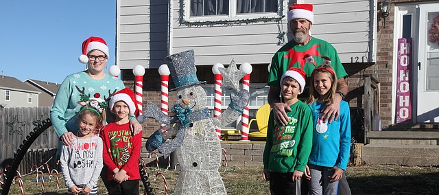 The Burge family stands oustide their festive home. Pictured, from left, are Teresa with Betsey, 7, and Jakob, 8, and then Tim with Trent, 9, and Lilly, 10.
