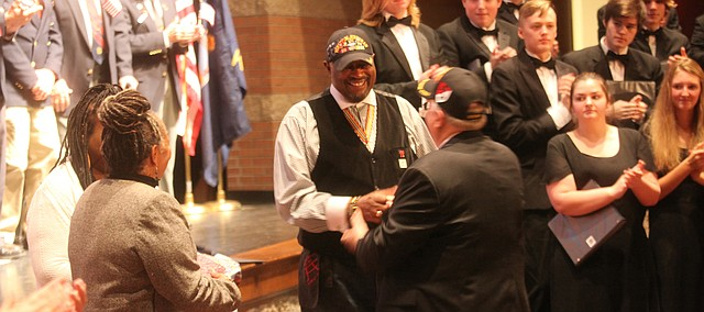 Sgt. Jerry Jarrett is congratulated after being presented a Quilt of Valor during the inaugural Tonganoxie USD 464 Veterans Day Program at the Tonganoxie Performing Arts Center on the Tonganoxie High School campus this past November.