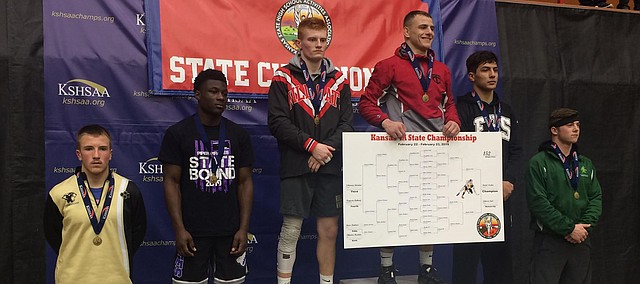 Tonganoxie High senior Korbin Riedel stands at the podium with his championship bracket. Riedel capped an undefeated season with Tonganoxie's first state wrestling champion in school history.