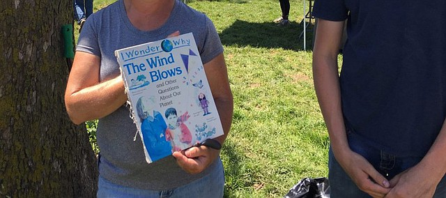 Lisa Leach holds a cover of a book that was found in the field at Lin-Crest Farm. The book didn't belong to them, but it blew in during the tornado on May 28, 2019. Jacob Raber, of Gridley, Ill., right, is a family friend from the show-cattle circuit who came to help with the tornado cleanup.