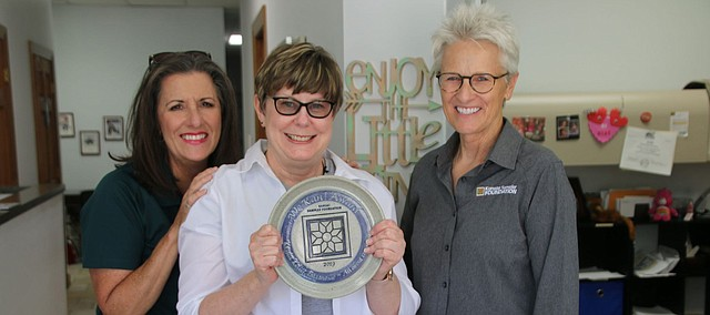 Keyta Kelly gathers with WenDee Rowe, left, and Mari Penner, right, with the Kansas Sampler Foundation. Penner and Rowe presented Kelly with a We Kan! Award on Thursday in Tonganoxie.