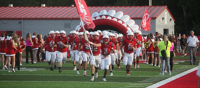 Tonganoxie High football players charge on to the field during pregame festivities Friday at Tonganoxie's Beatty Field. THS won, 49-28, against Basehor-Linwood in the first game of the season and inaugural American football game on the field.