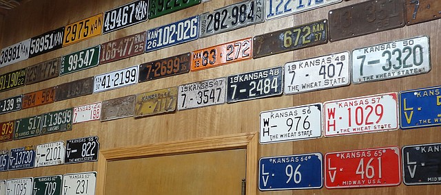 License plates galore adorn a wall in the Tonganoxie Community Historical Society Museum. Brady Mikijanis will present a program on the history of vehicle license plates in Kansas and Tonganoxie later this month. The plate display is a new exhibit at the museum. TCHS will have a grand opening of the exhibit, which will be a permanent collection at the historic site campus.