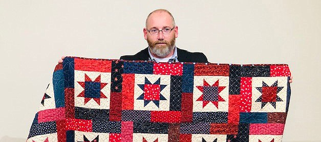 Tonganoxie veteran Michael Wehmeyer receives a Quilt of Valor on Nov. 11 from his Farm Bureau colleagues in Manhattan.