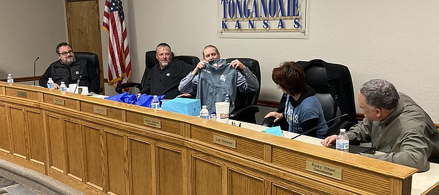 Jason Ward shows up a fishing shirt he was given at the end of Monday's Tonganoxie City Council meeting. Colleagues presented him with the shirt in recognition of his many years of serving on the Tonganoxie City Council.