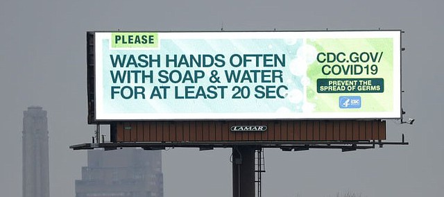 A billboard along Interstate 35 displays tips to help people prevent the spread of the novel coronavirus Monday, March 16, 2020, in Kansas City, Kan. (AP Photo/Charlie Riedel)