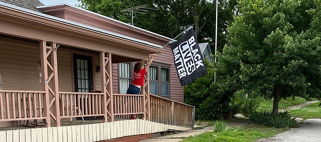 Kate Frick puts up a Black Lives Matter flag May 30 at Myers Hotel Bar. Someone took the flag a few days later