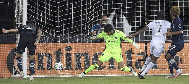 Minnesota United midfielder Kevin Molino (7) scores past Sporting Kansas City goalkeeper Richard Sanchez (1) during the second half of an MLS soccer match, Sunday, July 12, 2020, in Kissimmee, Fla. Minnesota United won 2-1. (AP Photo/Phelan M. Ebenhack)