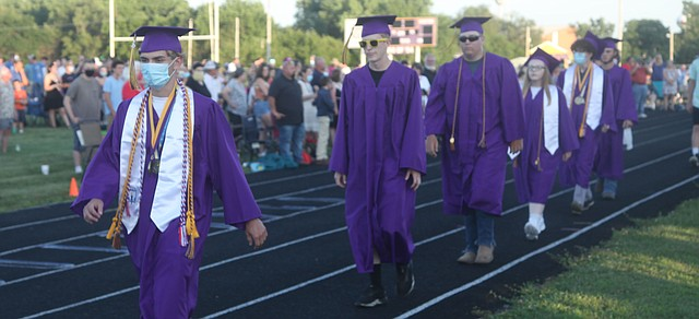 Dakota Schupp makes his way into Saturday's McLouth High School graduation ceremony at Stan Braksick Sports Complex in style with colorful socks and yellow Crocs. Schupp was one of three co-valedictorians in the MHS Class of 2020.