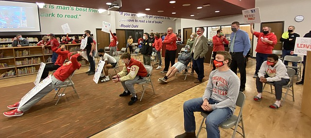 Visitors look on during a special Tonganoxie USD 464 school board meeting Monday at the Tonganoxie Elementary School library. The meeting lasted nearly 2 1/2 hours before the board ultimately agreed to allow extracurricular activities to move forward.