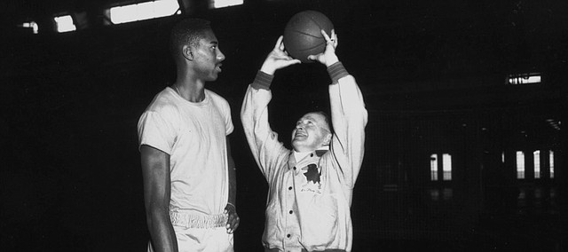 University of Kansas basketball coach Phog Allen holds the ball over new recruit Wilt Chamberlain's head in an early practice after Chamberlain arrived at KU in 1955 as a freshman. Chamberlain scored 42 points in his freshman opener against the KU varsity.