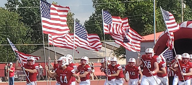 Tonganoxie High football players run onto the field carrying American flags Friday before their game against Basehor-Linwood. THS was honoring and remembering those who fought in the war in Afghanistan. The United States first launched military efforts in Afghanistan less than a month after the terrorist attacks on American soil on Sept. 1, 2001. The 20th anniversary of 9-11 is this Saturday.