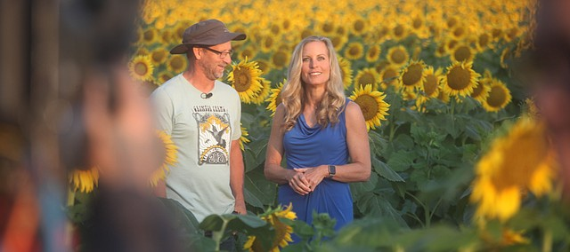 """Ted Grinter stands with Becky Worley during an interview Thursday, Sept. 9, 2021, in one of the sunflower fields at Grinter Farms 4 miles south of Tonganoxie. Worley featured Grinter Farms during a Rise and Shine segment profiling Kansas on """"Good Morning America."""" ABC's national morning show is highlighting all 50 states. Kansas marked state No. 30 in the series."""