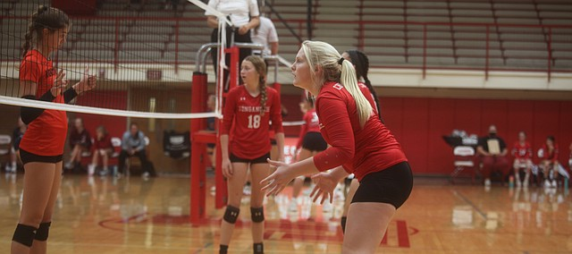 Tonganoxie High's Jordan Vorbeck is locked in awaiting a Shawnee Mission Northwest serve Saturday during a semifinal match at the Tonganoxie Invitational. The Cougars outlasted the Chieftains and then defeated Ottawa fro the tournament title. Looking on is Kasia Baldock (18).