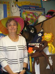 Veltum wear her sun hat (for when her students are too bright) in front of her hat collection.