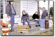 Rachel Coleman puts an old 45-record in a box as her sister, Hannah, reads the title of another record to their mother, Tina Coleman, as their father, Jerry Coleman watches. The family, whose home was struck by fire on Nov. 26, expects to move back into their home by Christmas.