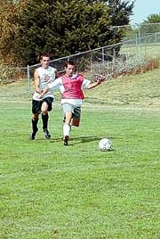 Jordan Hevel and Kyle Bray race to the ball at Monday's De Soto High School practice. The soccer team opens at 4:30 p.m. Friday at Immaculata in Leavenworth.