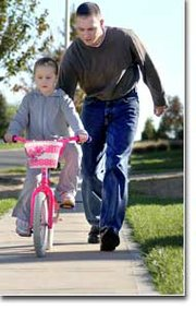 Tony Rider is home from the war in Iraq and is spending some of his free time to help his daughter Jordan ride a bike without training wheels.