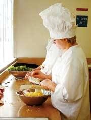 Kasey Place of De Soto High School grates Gouda cheese during her culinary arts class at Eudora's vocational education center. Students in the program were preparing for their first community dinner Oct. 16. Each student will take a turn as host or hostess, meaning he or she gets to pick the menu.