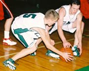 Brady Seaman and Pete Crall go to the floor for a loose ball in Tuesday's De Soto High School Wildcats home win against Lansing. The win was the team's second in a row.