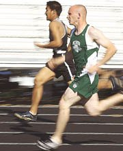 Justin Bartholomew of De Soto High School matches strides with an opponent in the 100-meter dash Tuesday during a track meet at the high school. Bartholomew didn't place in that race but finished sixth in the 200 meters