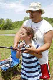 Mariah Seifert, of Bonner Springs, reels in a catch with the help of her uncle Eddie Padilla, of the Sac and Fox Reservation near Horton. The girl was one of numerous youngsters taking advantage of the opening of the lake at Kill Creek Regional Park for fishing by those 15 years old or younger.