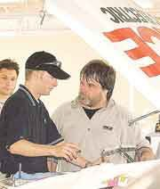 Team Chick driver Eric Jones, center, talks to truck chief and chassis set-up man Bud Haefele about the truck's performance while mechanic Louis Paternico looks on.