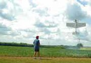 John Wells walks behind his hovering radio-controlled model airplane Friday at the 95th Street Flying Group's new home in De Soto's east bottoms. Forty-three club members, the group's limit, fly there at various times during the week.