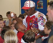 Students swarm baseball legend Buck O'Neil after he spoke with Lansing Elementary third-graders on Oct. 25.  O'Neil played and coached for the Kansas City Monarchs of the Negro Leagues and was the first black coach in Major League Baseball.