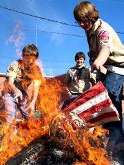 Daniel Wranich and Tim Lamborn throw a flag into the fire as a part of a flag retirement ceremony on Saturday November 13 at the Veterans of Foreign Wars building in Leavenworth.