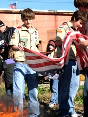 Daniel Wranich and Jonathan Beaver get ready to throw a flag into the fire as a part of a flag retirement ceremony for their Boy Scout troop 165 on Saturday November 13 at the Leavenworth Veterans of Foreign Wars building. The VFWs helped the troop discard of more than 100 flags respectfully.