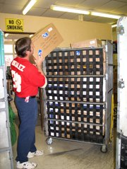 Lansing Post Office clerk Kenny Howard loads a package bound for Iraq into a cart.