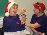 "Rosemary Wasserman, left, exclaims at the holiday ornament she unwrapped during the Lansing Red Hat Movers and Shakers' Christmas party. Also admiring the ornament is Laura Barnes. Twenty-one members of the group ""exchanged"" decorations in an elaborate holiday tradition Tuesday at the Lansing Activity Center."